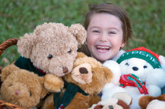 Girl with teddy bears. Teddy bears galore! Happy cute little girl surrounded by lots of brown and white teddy bears Royalty Free Stock Image