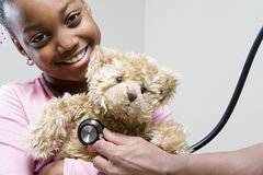 Girl and teddy with stethoscope Royalty Free Stock Image