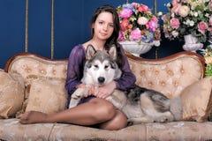 Girl teen and dog malamute on sofa Royalty Free Stock Image