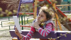 Girl teen doing selfie on white tablet on the playground stock video footage