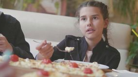 Girl teen eats pizza in cafe slow motion video. children eat pizza a delicious pizza. company of people lifestyle
