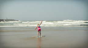Girl or teen learning to ride a skimboard on the Oregon coast Royalty Free Stock Photos