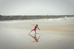 Girl or teen learning to ride a skimboard on the Oregon coast Royalty Free Stock Photo