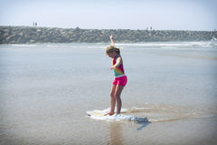 Girl or teen learning to ride a skimboard on the Oregon coast Stock Photo