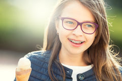 Girl. Teen. Pre teen. Girl with ice cream. Girl with glasses. Girl with teeth braces. Young cute caucasian blond girl wearing teeth braces and glasses Stock Image