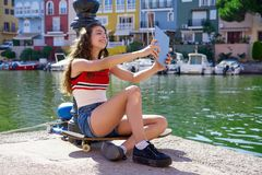 Girl teen with skateboard and tablet selfie stock images