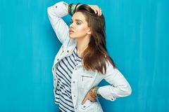 Girl in teen style with long hair standing against blue wall bac. K. Studio fashion portrait Stock Photography