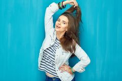 Girl in teen style with long hair standing against blue wall bac. K. Studio fashion portrait Royalty Free Stock Image