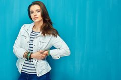 Girl in teen style with long hair standing against blue wall bac. K. Studio fashion portrait Royalty Free Stock Photo