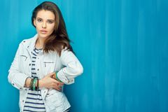 Girl in teen style with long hair standing against blue wall bac. K. Studio fashion portrait Royalty Free Stock Photography