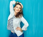 Girl in teen style with long hair standing against blue wall bac. K. Studio fashion portrait Stock Photos