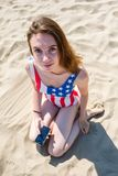 Girl teen in a swimsuit with a print of the USA flag sits on the sand with cellphone on her hand. Girl in a swimsuit with a print of the USA flag sits on the Royalty Free Stock Photography