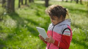 Girl teen with a tablet in spring on background of green grass in the forest plays in the online game stock video