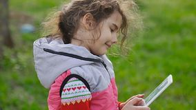 Girl teen with tablet in spring on background of green grass in the forest plays in the online game stock video footage