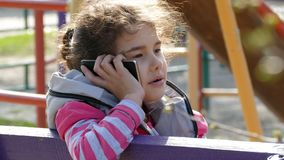 Girl teen talking on a smartphone phone in the playground stock footage