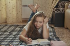 Girl teen who spend time at home drawing while lying on the floor. Youth pastime Stock Photo