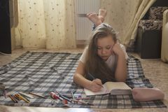 Girl teen who spend time at home drawing while lying on the floor. Youth pastime Stock Photography
