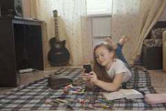Girl teen who spend time at home drawing sketches in a notebook and using her smartphone while lying on the floor. Youth pastime Royalty Free Stock Photos