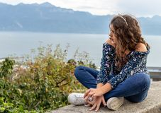 Girl. Teenage. View. Sitting. Outdoor scene. Young teenage girl sitting on the wall with beautiful Geneva lake on the background royalty free stock image