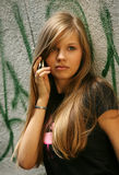 Girl - teenager. The young girl with phone on a background of a wall with graffiti Stock Photography