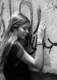 Girl - teenager. The young girl with phone on a background of a wall with graffiti Royalty Free Stock Image