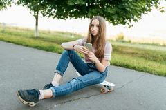 Free Girl Teenager 9-11 Years Old, Sits On Board In Hands Of Phone. In Summer In City In Casual Jeans And A Pink T-shirt Stock Images - 138481314