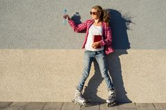 Girl teenager for an active lifestyle. Poses on the background of the wall is shod in the quad roller skates, holds a book and a b royalty free stock photos