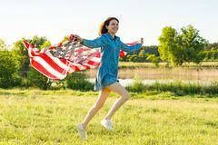 Girl teenager with American flag running through the summer green meadow at sunset. Nature background, rural landscape.  Royalty Free Stock Images