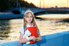 Girl teenager blonde holding a toy bear at sunset in a city royalty free stock photography