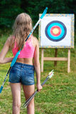Girl teenager with bow and arrows in front of target Royalty Free Stock Photography