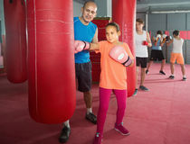 Girl teenager at boxing workout on punching bag. With instructor Stock Photography