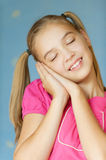 Girl-teenager she closed her eyes. Beautiful blue-eyed laughing girl-teenager she closed her eyes and put his hands behind his head, on blue background Royalty Free Stock Photos