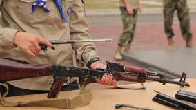 Girl Collects Assault Rifle. Girl teenager collects firearms Kalashnikov assault rifle weapon stock video