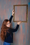 Girl teenager corrects an empty picture frame. Stock Photography