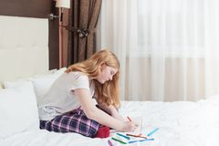 Girl teenager draws in bed Stock Photography