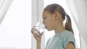 Girl teenager drinking water from glass on home kitchen on window background. Girl teenager drinking clear water from glass on home kitchen on window background royalty free stock image