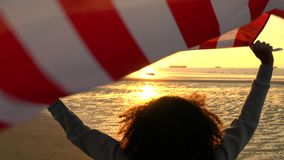 Girl teenager female young woman holding an American US Stars and Stripes flag on a beach at sunset or sunrise. 4K video clip of mixed race African American girl stock video footage