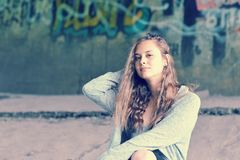 Girl teenager with flowing brown hair sitting against concrete w Stock Image