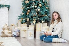 Girl teenager with a gift in her hands. Crouched beside the decorated Christmas tree Royalty Free Stock Photo
