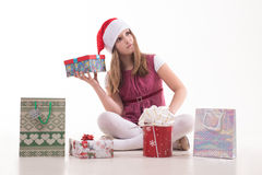 Girl teenager with a gift in a Santa hat. Girl baby with a gift in a Santa hat Royalty Free Stock Images