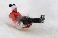 Girl teenager going down the hill on a sled, flew up on a hummock. royalty free stock photos