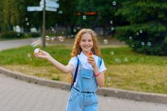 Girl teenager happy smiling blows soap bubbles royalty free stock image