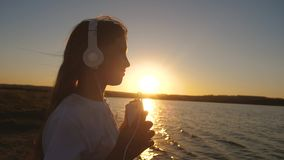 Girl teenager in headphones with phone near water at sunset. Slow motion. Girl teenager in headphones with phone near water at sunset listening to music. Slow stock footage