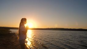 Girl teenager headphones and with phone at sunset. Girl teenager in headphones with phone near water at sunset listening to music and dancing stock video