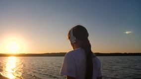 Girl teenager in headphones near water at sunset. Girl teenager in headphones by water at sunset red sun listening to music stock footage