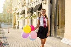 Girl teenager high school student with balloons. In school uniform with glasses goes along the city street. Start of classes Stock Images