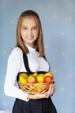 Girl-teenager holding basket. Beautiful blue-eyed smiling girl-teenager holding basket with apples, on blue background Stock Photos