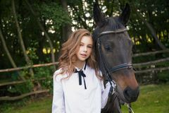 Girl teenager with a horse. Girl teenager and black horse in a park in a summer day Stock Image
