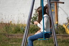 Girl Teenager In A White Jacket Sitting On A Swing With A Mobile Phone In Their Hands In The Courtyard Stock Images