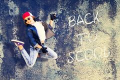 Girl teenager in the jump. Denim clothing. Baseball cap. Against the background of the old concrete wall. Inscription Back to Scho royalty free stock photos